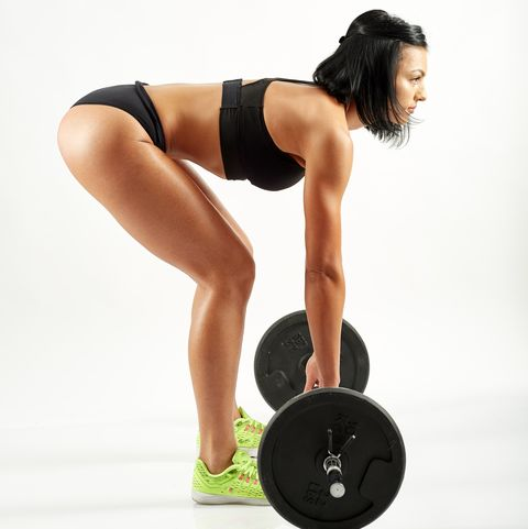 Young woman doing deadlift with barbell