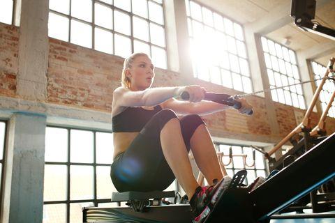 Jovem mulher fazendo exercícios na máquina de fitness