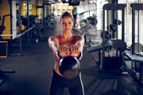 Mujer joven haciendo ejercicio de pesas rusas en el gimnasio