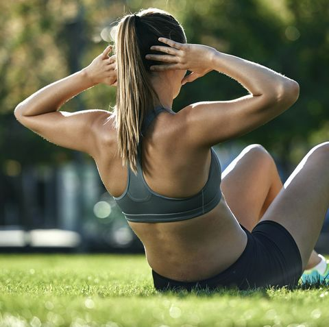 young woman doing sit ups in park