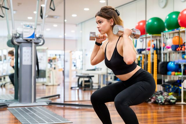 young woman doing squats whilst holding weights
