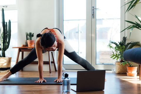young woman doing stretching exercise in front of laptop at home
