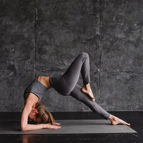Young woman doing yoga on a gray background