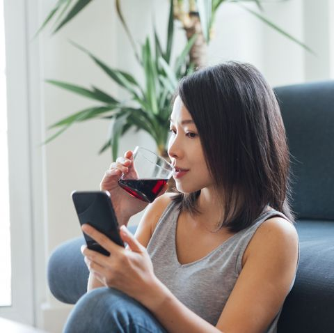 young woman drinking and using smartphone at home