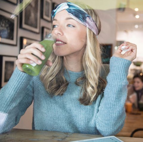 young woman drinking vegetable juice at cafe window seat