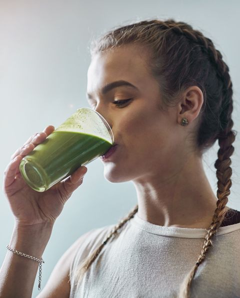 Young woman drinking vegetable smoothie in kitchen
