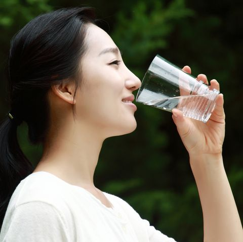 young woman drinking water in a park image