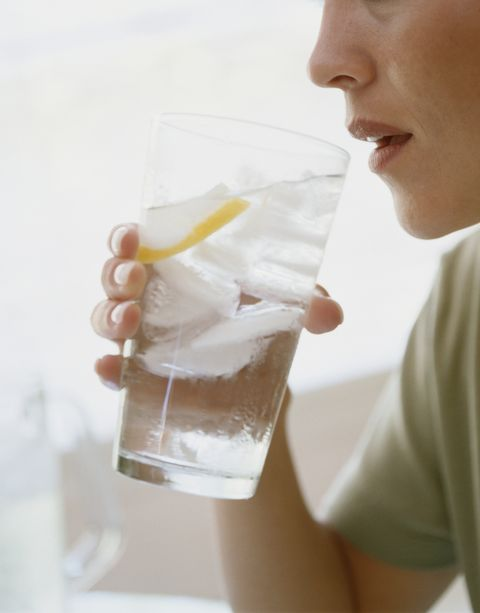 young woman drinking water, side view, close up