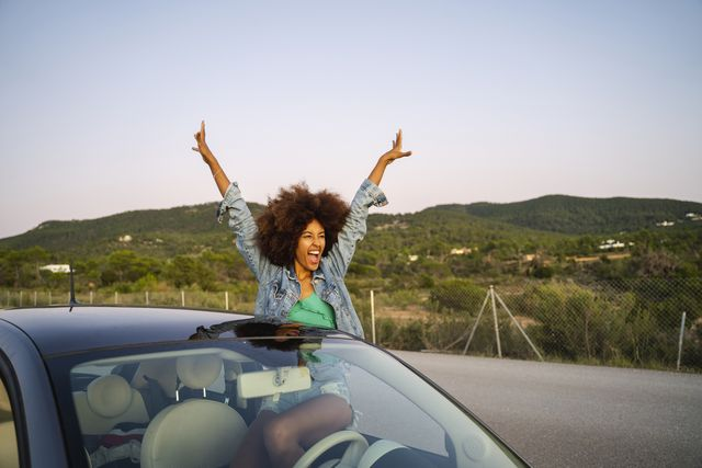 young woman during road trip with raised arms
