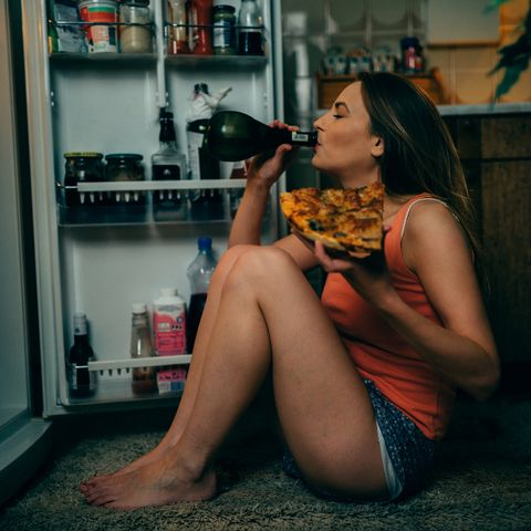 young woman eating and drinking in the kitchen late night