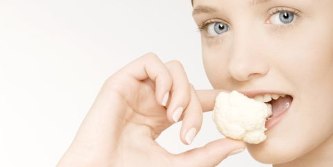 Young woman eating cauliflower