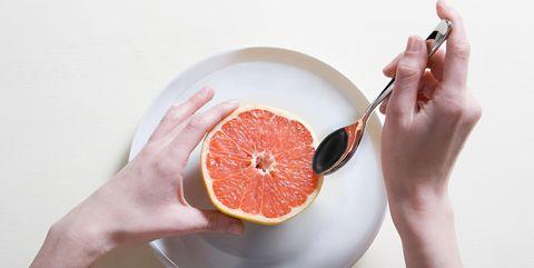 young woman eating grapefruit
