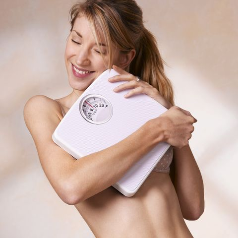 young woman embracing bathroom scales, close up