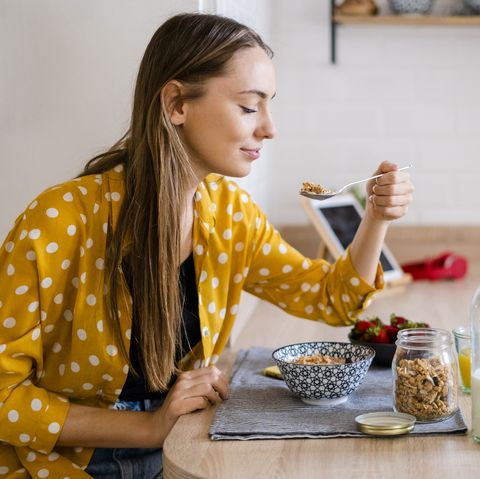 young woman enjoying breakfast in kitchen at home