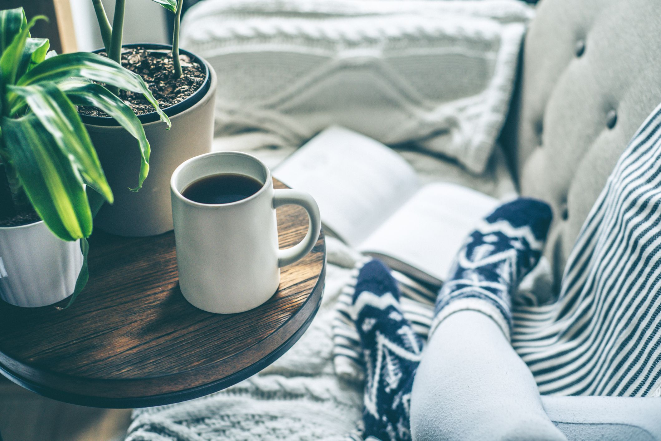 Woman enjoying coffee and relaxing on a sofa with a book