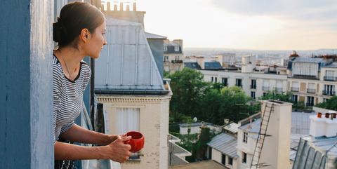 young woman enjoying the view from a parisian apartment