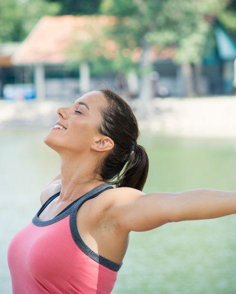 Young woman enjoys in fresh air near lake