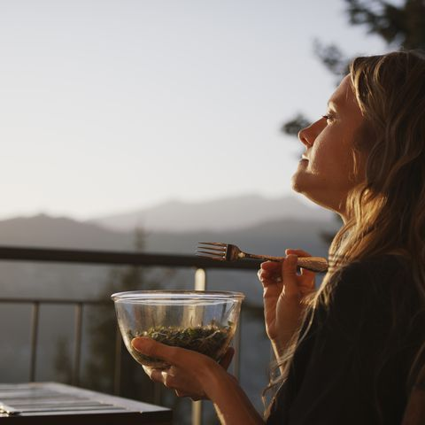 young woman enjoys salad in the sunshine on her patio