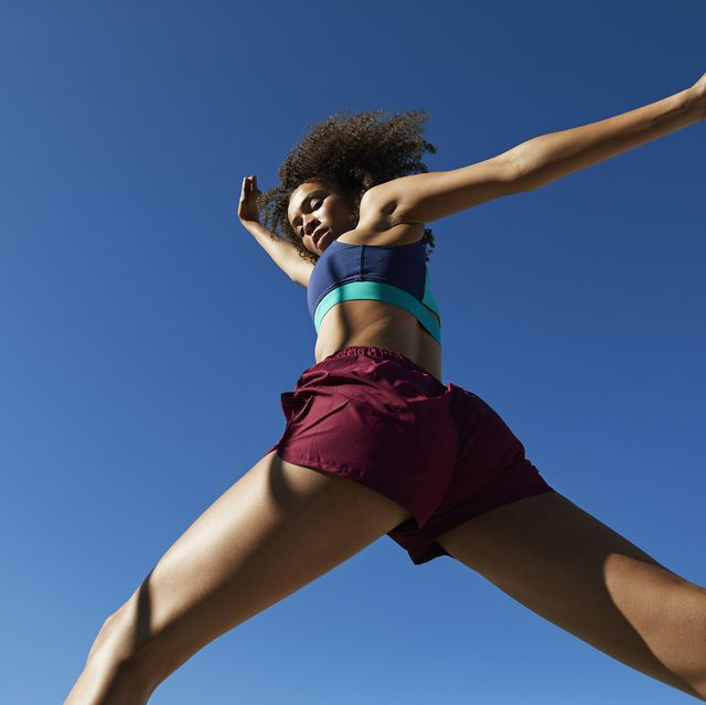 young woman exercising against clear sky
