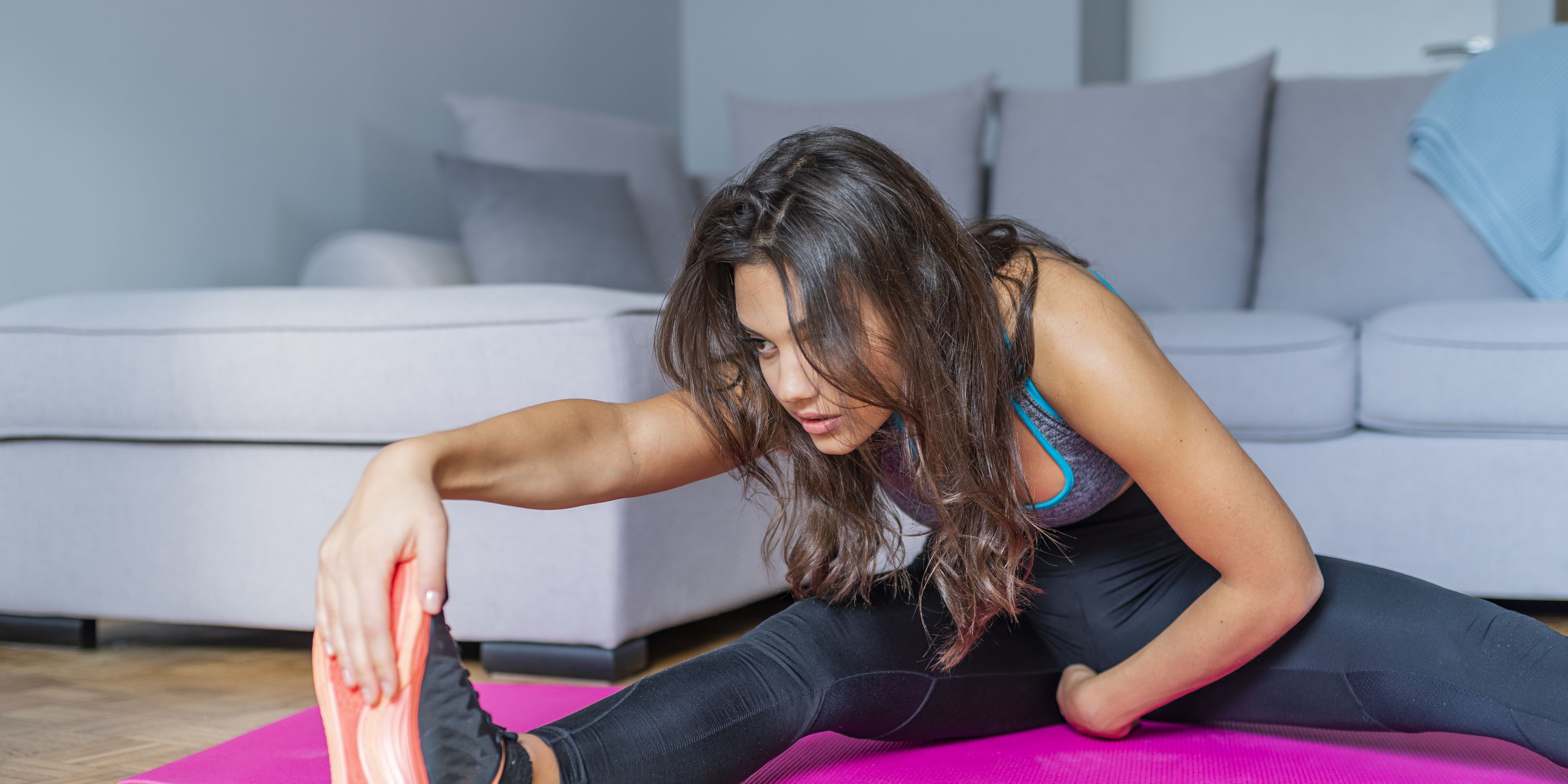 Young woman exercising at home, stretching