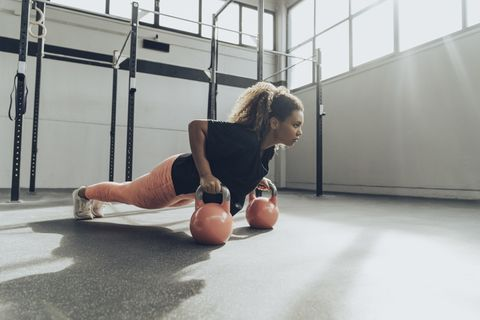 young woman exercising with kettlebells in gym