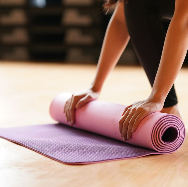 young woman folding yoga mat  after class end