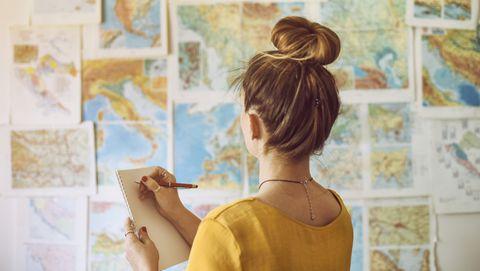 young woman handwriting at notebook while looking at map