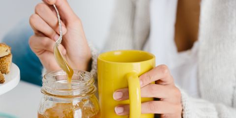 Young woman having honey drink