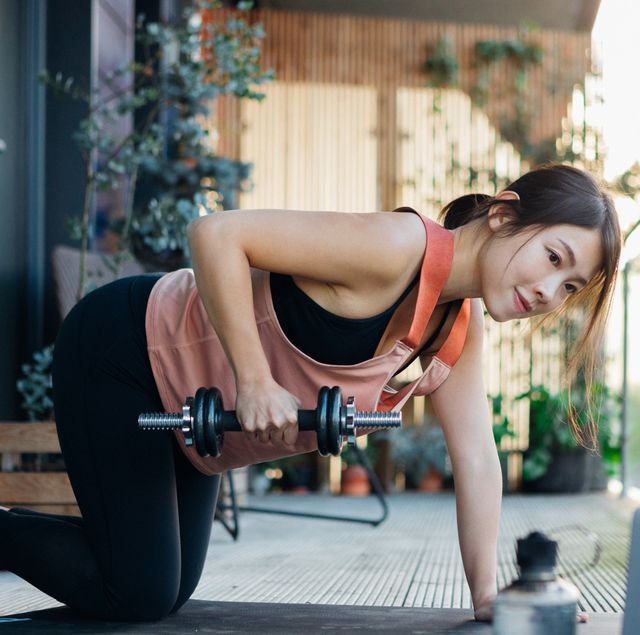 young woman holding dumbbells in front of laptop on the balcony