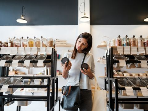 una mujer joven sostiene botes reutilizables en una tienda