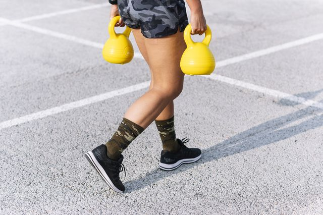 young woman holding kettlebells while walking on road