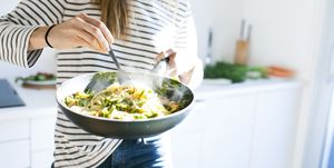 Young woman holding pan with vegan pasta dish
