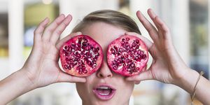 Young woman holding pomegranate slices as glasses