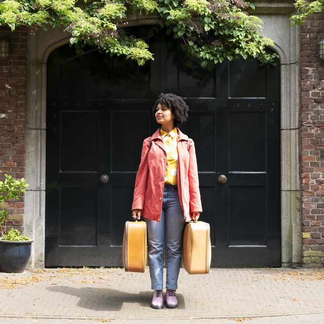 a young woman holding suitcases
