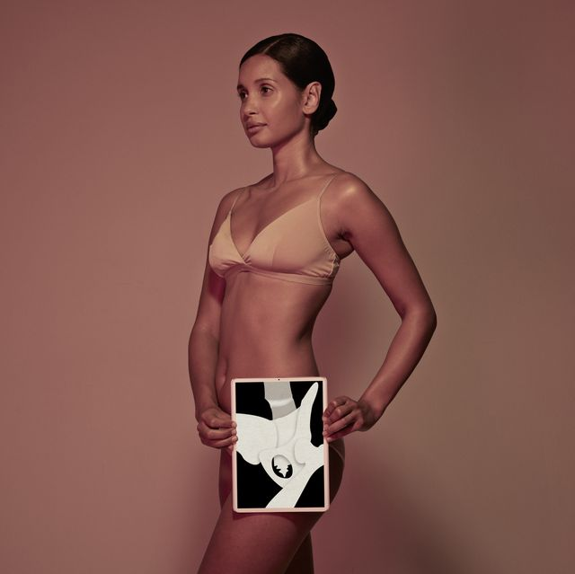 young woman holding tablet in front of body to display hip bone
