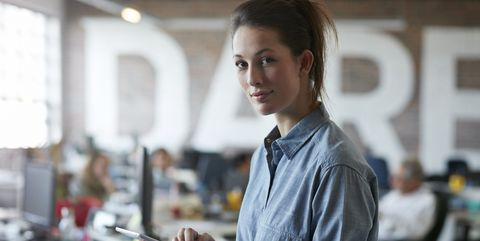 Young woman holding tablet, in open office
