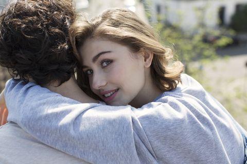 Young woman hugging man