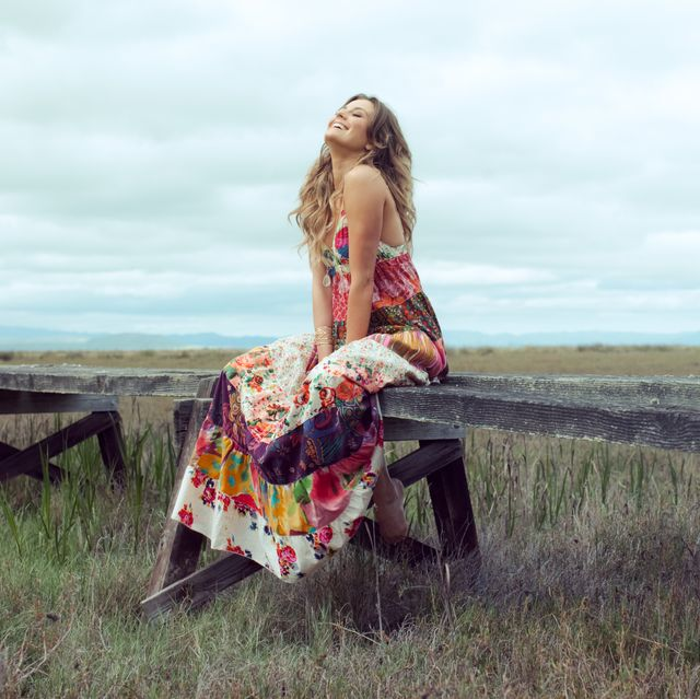 young woman in boho maxi dress sitting on elevated wooden walkway in landscape