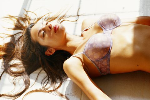 young woman in bra lying on floor, elevated view