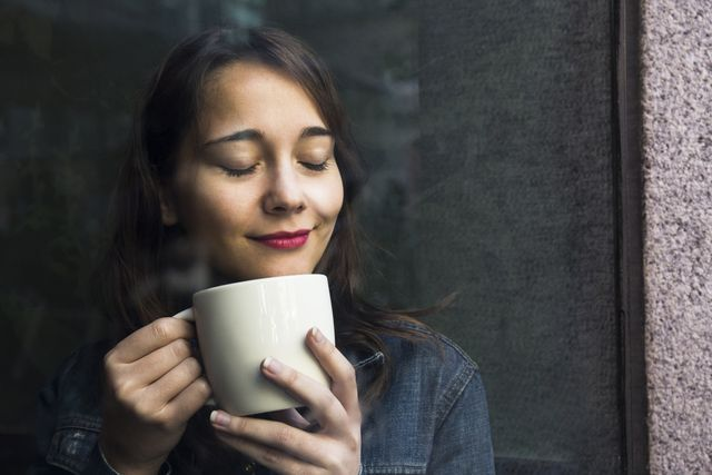 young woman in cafe with cup of coffee and closed eyes
