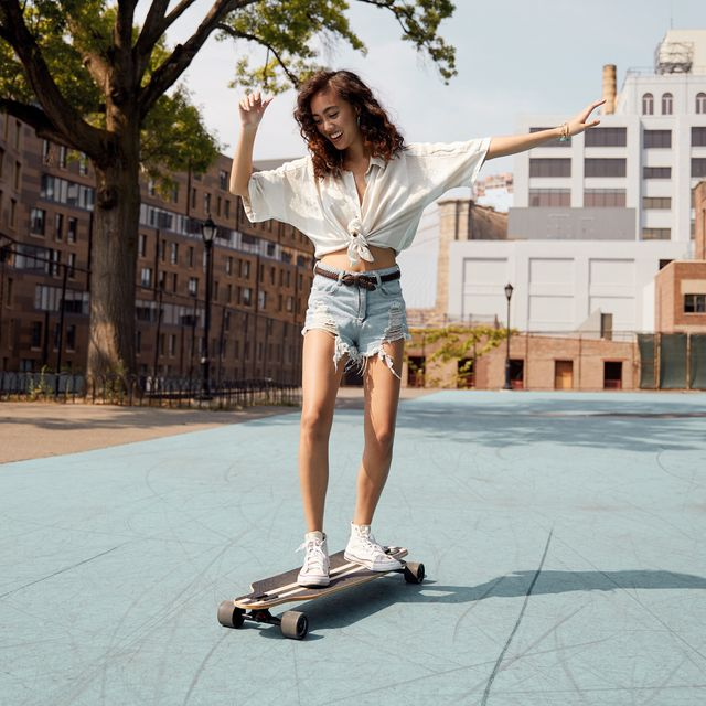 young woman in city on skateboard