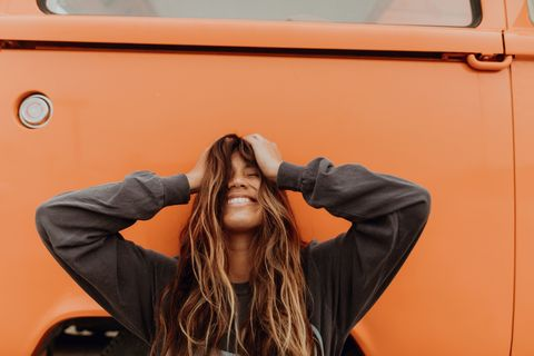Young woman in front of orange recreational vehicle at beach, portrait, Jalama, California, USA