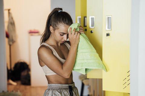 Mujer limpiándose el rostro en el vestuario del gimnasio