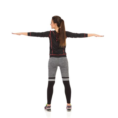 young woman in sports clothes is standing with arms outstretched rear view