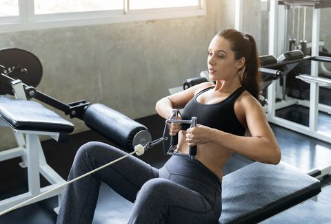 young woman in sportswear in the gym, training hard and pulling weights in seated cable row machine, athlete makes low cable pulley row seated in the gym, bodybuilder, sport fitness and muscles