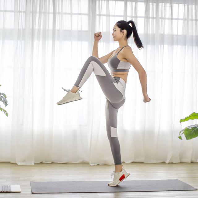 young  woman in sportswear watching online video with fitness exercises on laptop
