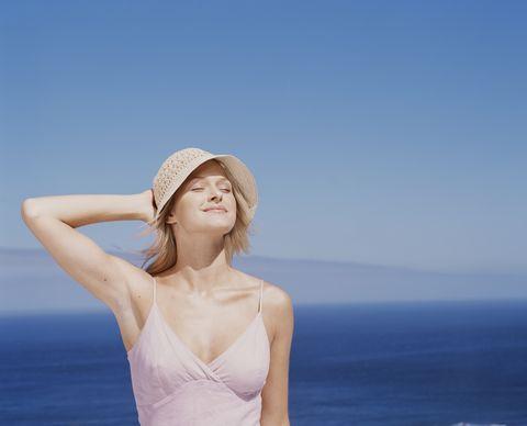 chica joven con top y sombrero mira hacia el sol en un paisaje frente al mar