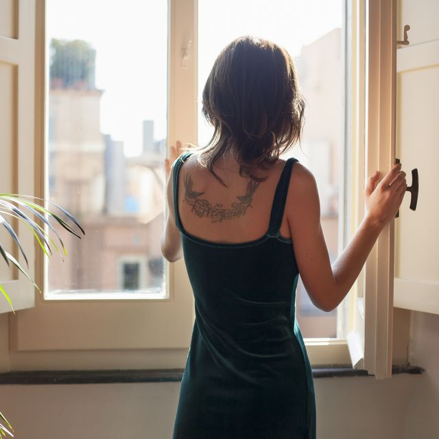 young woman in velvet dress opening window, rear view showing tattoo