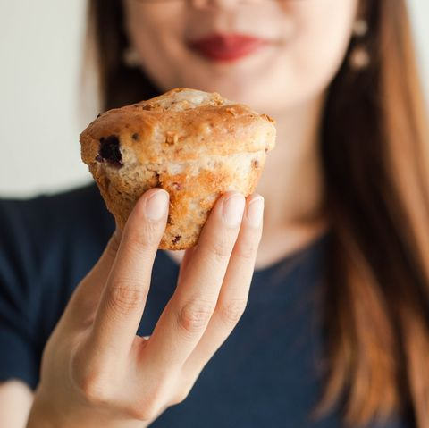 a young woman is eating a fruit muffin