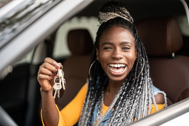 young woman is excited about new car